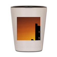 sun setting behind a tall structure ref Shot Glass