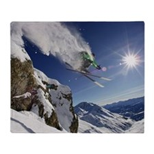 Skier in midair on snowy mountain Throw Blanket