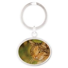Green-eyed cat in the grass Oval Keychain