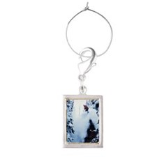 A snowboarder jumping off a cl Portrait Wine Charm