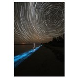 Star trails over bioluminescence in waves on the s