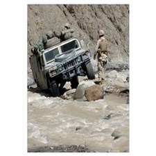 A US Marine guiding a Humvee through a river in Kh
