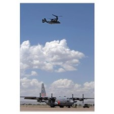 A CV22 Osprey flies over a C130 Hercules