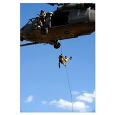 A pararescueman rappels from an HH60 Pavehawk heli