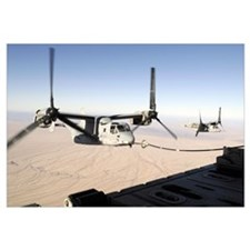A MV22 Osprey refuels midflight while another wait
