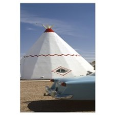Car with a teepee in the background Wigwam Motel R
