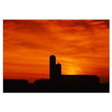 Silhouette of a barn and a silo at sunset, Pennsyl