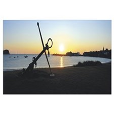 Silhouette of an anchor on the beach at sunrise, N