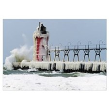 Wave crashing on snow-covered South Pier lighthous