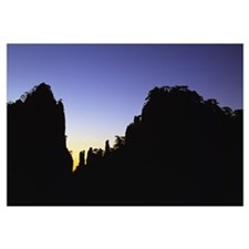 Sunset light behind silhouetted Huangshan Mountain