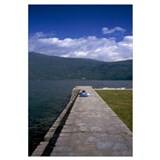 Rear view of a child sitting on a stone wall, Lake