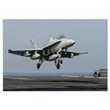 A US Navy F/A-18C Hornet prepares to land aboard U