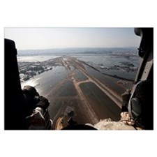 Airmen fly over the Sendai Airport in Japan to sur