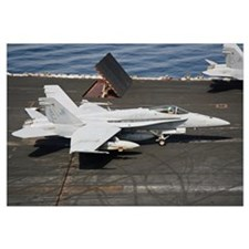 An F/A-18C Hornet sits ready on the flight deck of
