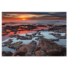 Tidal pools reflect the sunrise colors during the