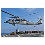 Sailors attach a cargo pennant to a MH-60S Sea Haw
