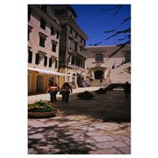 Two women walking in front of a courtyard in Corfu