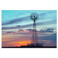 Windmill producing electricity at sunset example o