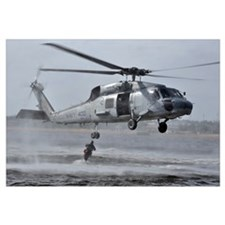 A search and rescue swimmer jumps from an SH-60F S