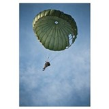 An Airman descends through the sky with parachute