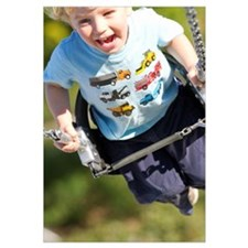 Young Boy Smiling Swinging In A Swing At The Playg