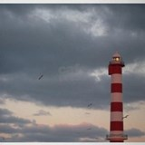 Lighthouse against cloudy sky Drinking Glass